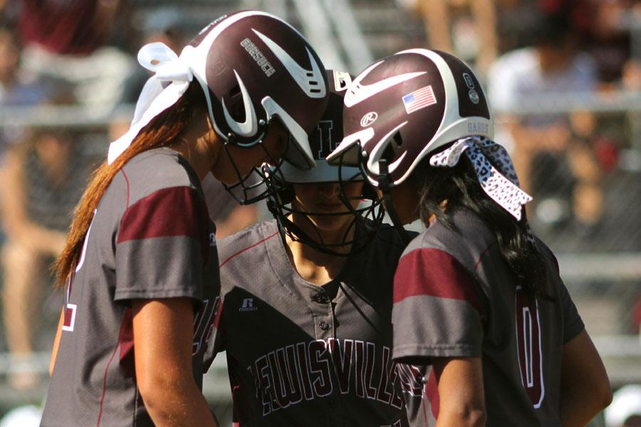 Sophomore Maribeth Gorsuch, junior Gaby Vasquez, and sophomore Tommi Godman huddled before the next inning began during the Mansfield Timeberview game on May 10.
