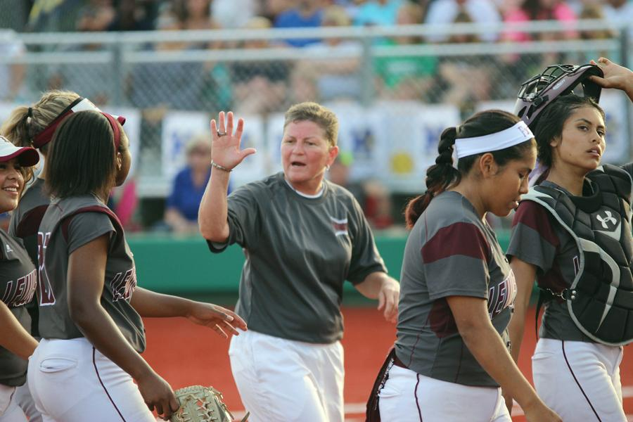 Head coach Lori Alexander offers a high five to third baseman A'Leecia Bell during Game 2 of the softball regional finals against Keller on lMay 29 in Argyle. Bell made the final out against San Benito on Friday in the Farmers 3-2 win to advance to the state final against Katy.