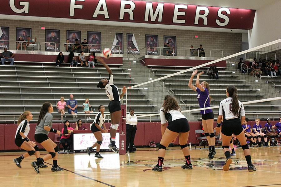 Sophomore Precious Ray (11) hits the ball over the net.