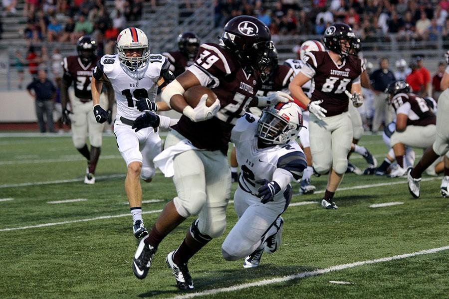 A player from the opposing team attempts to bring down senior Dontae McGee (29).