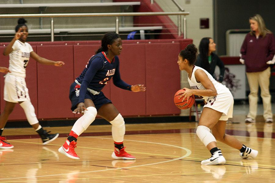 Sophomore McKenzie Bowie (15) crosses an Allen player in an attempt to make a better shot.