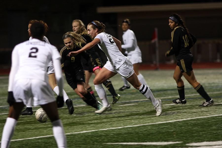 Senior Carli Arthurs (20) attempts to outrun the defender who tries to steal  the ball.