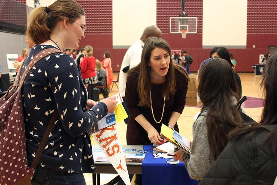 The representative from Oklahoma City University speaks to a student about her campus.
