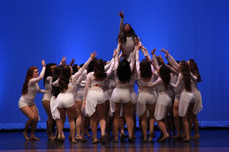 Senior Farmerette captain Jessica Brown is lifted up by her teammates during the song
