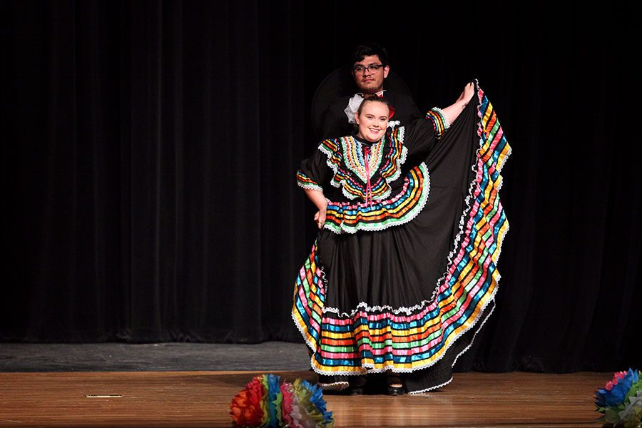 Alumnus Nathaniel Pierce stands behind alumna Hailey Bishop as she displays her traditional folklorico dress.