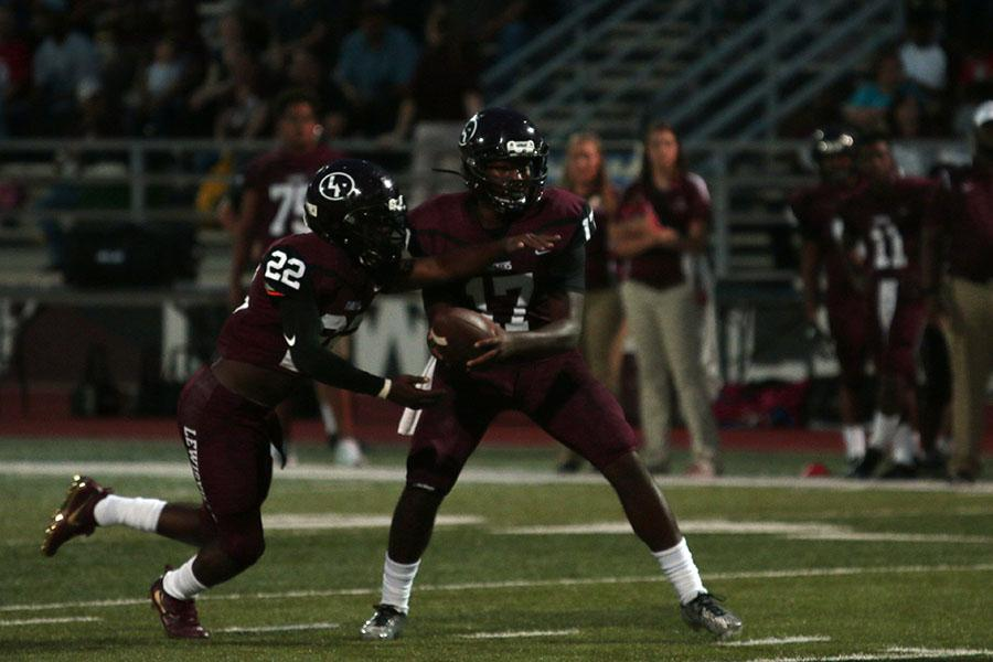 Quarterback Jarvis Brooks (17) hands the ball to running back Kwame Mickels (22) at the game on Friday, Aug. 26 against the Rowlett Eagles.
