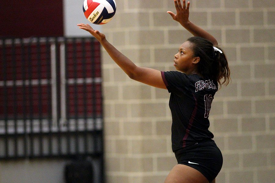 Senior Jayda Gibson (10) tosses the ball into the air in order to serve.