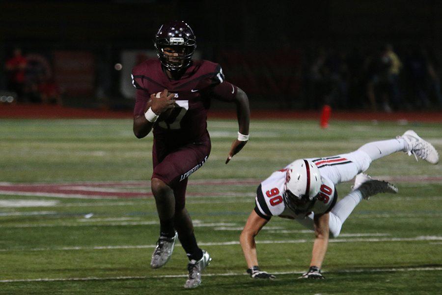 Senior quarterback Jarvis Brooks (17) runs the ball while Marcus High School's senior defensive end Brett Brown (90) misses the tackle.