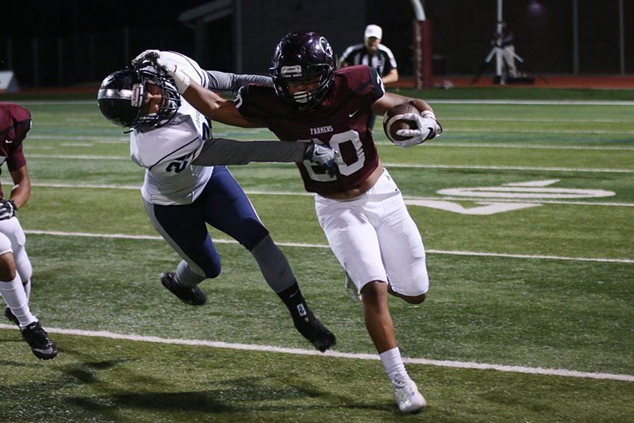 Junior running back De'Mondrick Hunter (20) blocks Flower Mound's defensive player while running the ball.