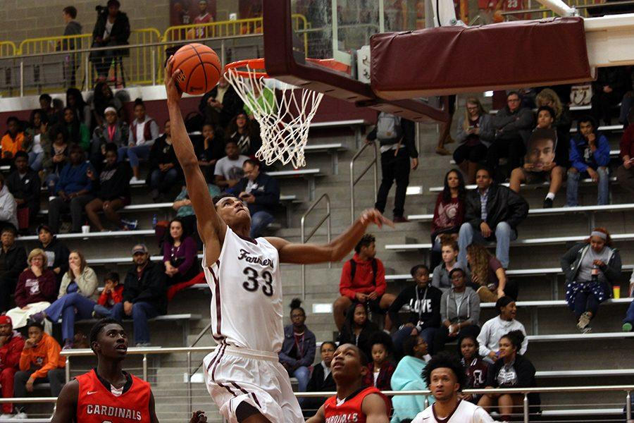 Junior Jydonn Griffith (33) dunks the ball to maintain the lead in the fourth quarter.