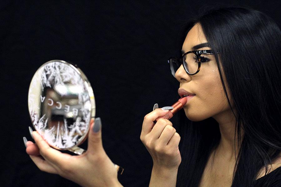 Senior Brysseida Fabian uses a BECCA cosmetics mirror to apply a MAC Cosmetics lipstick.