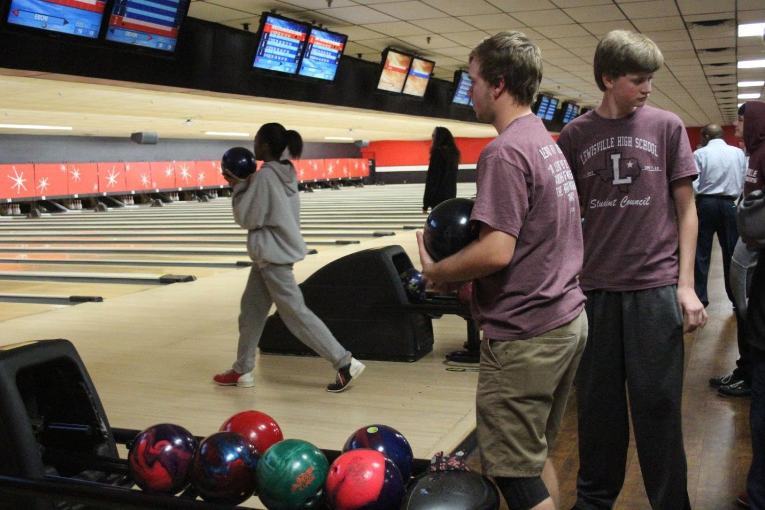 Senior Connor Mixson and junior Ben Olinger wait their turns to bowl as sophomore Eboni Boston bowls in the next lane.
