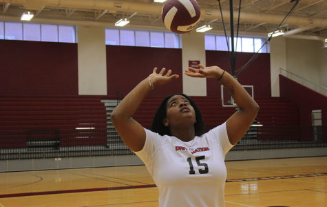 Senior Ryleigh Taylor sets a volleyball in the arena.