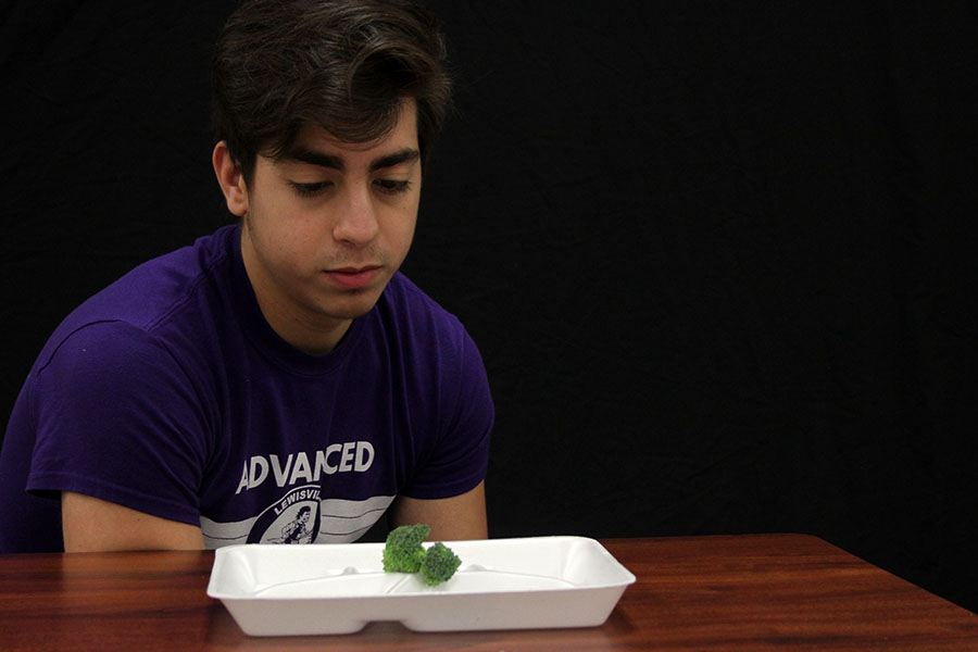 Junior Miguel Macias stares at a piece of broccoli to represent the eating habits of wrestlers.