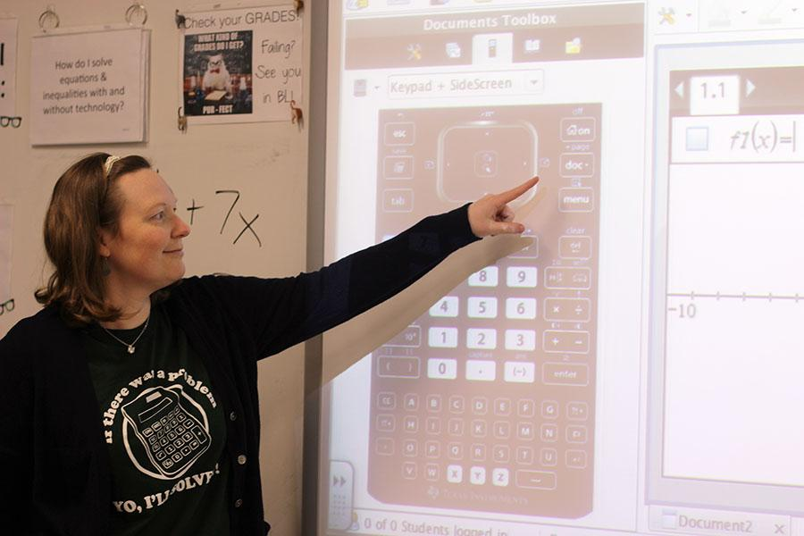 Algebra teacher Leigh Ann Mitchell assists students in solving an equation.