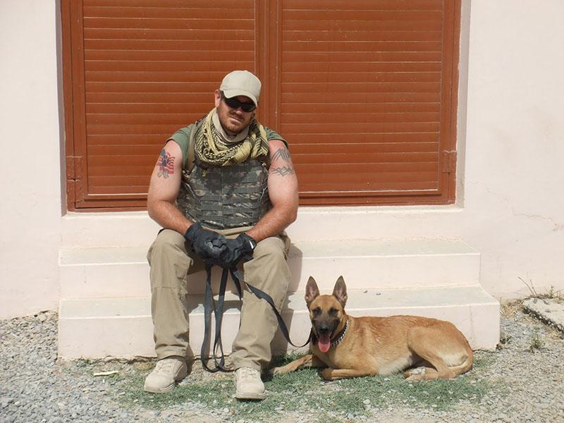 Former+Navy+sailor+and+law+enforcement+teacher+Travis+Mouser+sits+with+a+K-9+while+in+Afghanistan.+Courtesy+of+Travis+Mouser.+