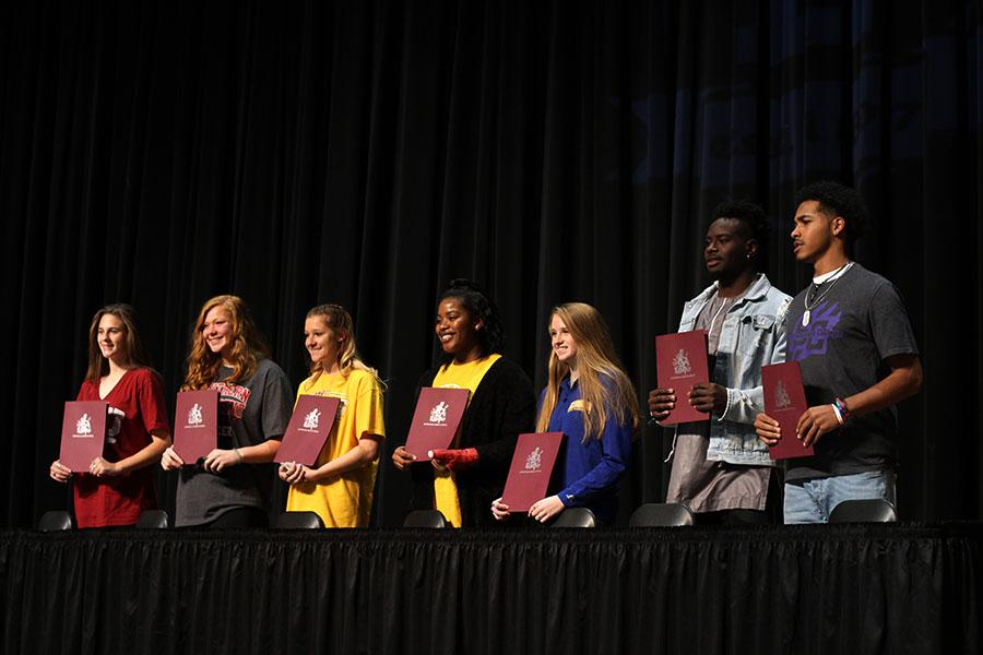 All seven National Signing Day honorees display their signed contracts on Wednesday, Feb. 7.