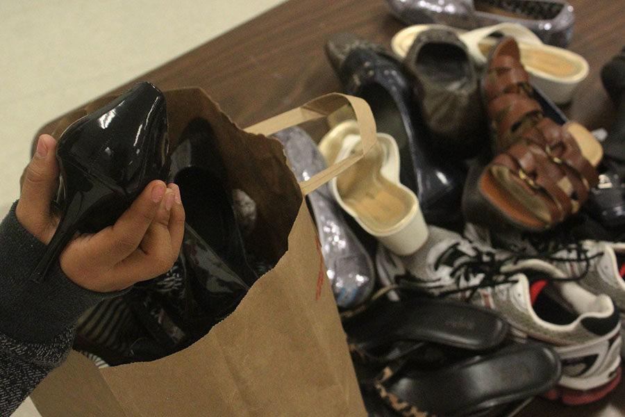 A student places a shoe into the bag for shipment.