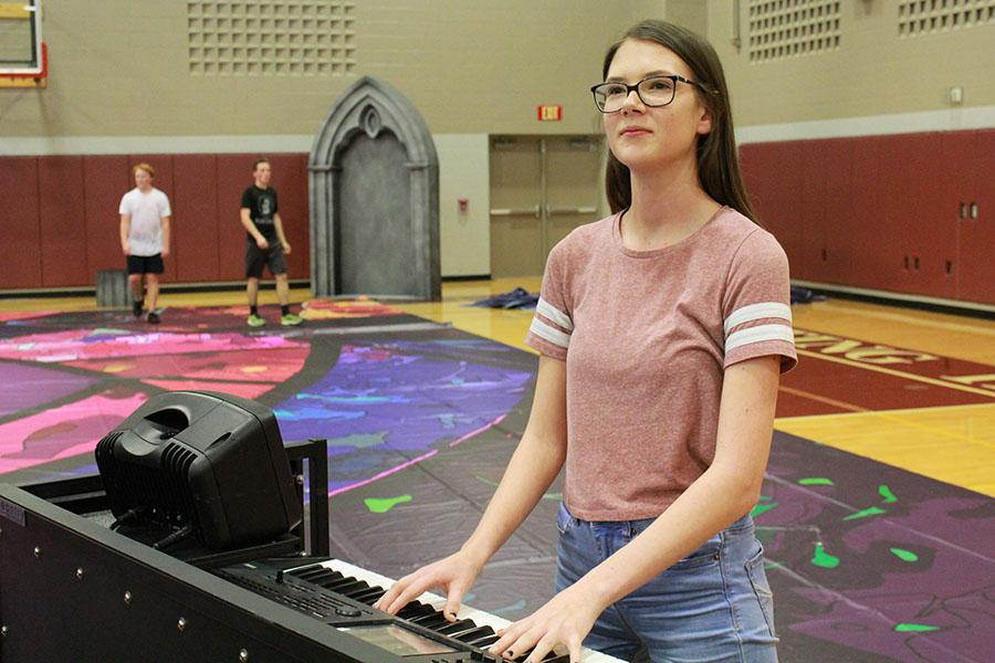 Senior Krista Anderson looks at the assistant director while playing keyboard during drumline practice.
