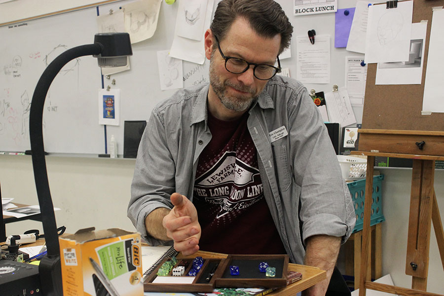 Killough art teacher Eric Champion rolls dice onto his own hand crafted box.