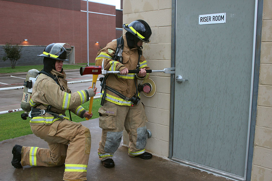 Marcus High School juniors Spencer Baltmanis and Ryan Moore attempt to jam open a door during practice.
