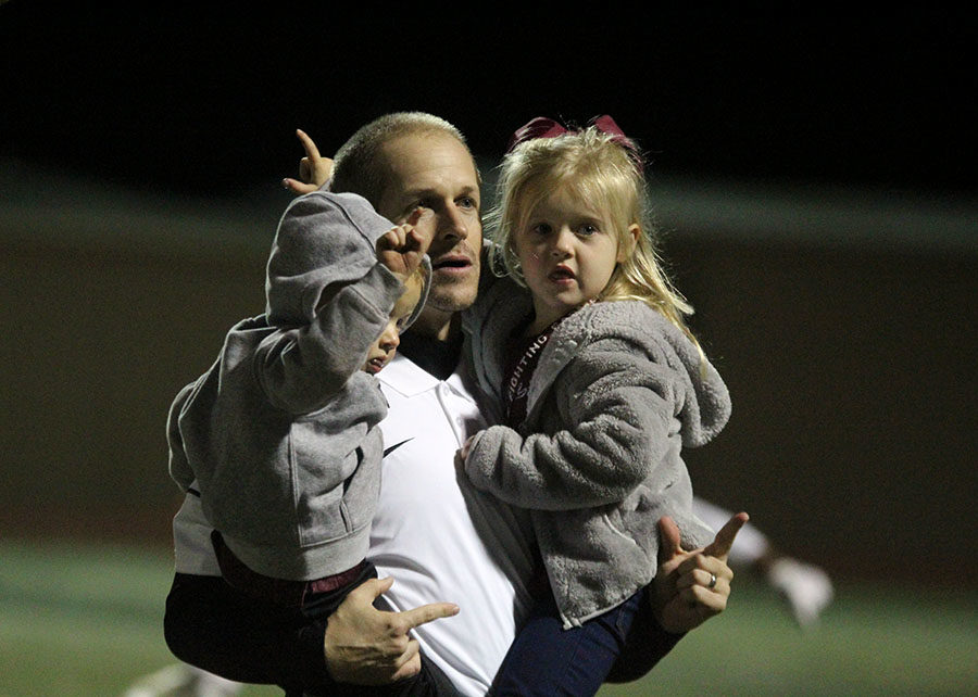 Head football coach Michael Odle sings the school song with his children.