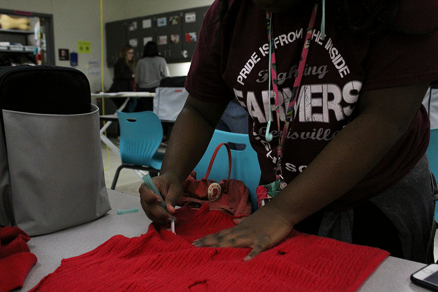 On Thursday, Nov. 29 during fashion club, junior Aliyah Rose distresses a sweater in preparation for the fashion show on Friday, Dec. 7.