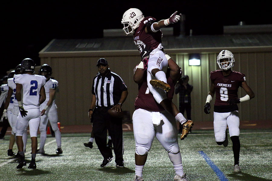 Senior Kwentin Huddleston (74) lifts senior Josh Lockhart (20) into the air to celebrate a touchdown at the home game against Hebron on Friday, Nov. 2. This touchdown put the overall score at 27-14.