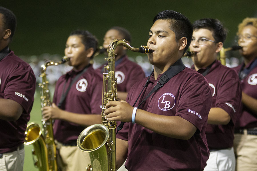 Senior Isaac Ramirez performs a song during halftime along with the rest of the saxophone section at the away game in the Grand Prairie stadium on Friday, Aug. 31.
