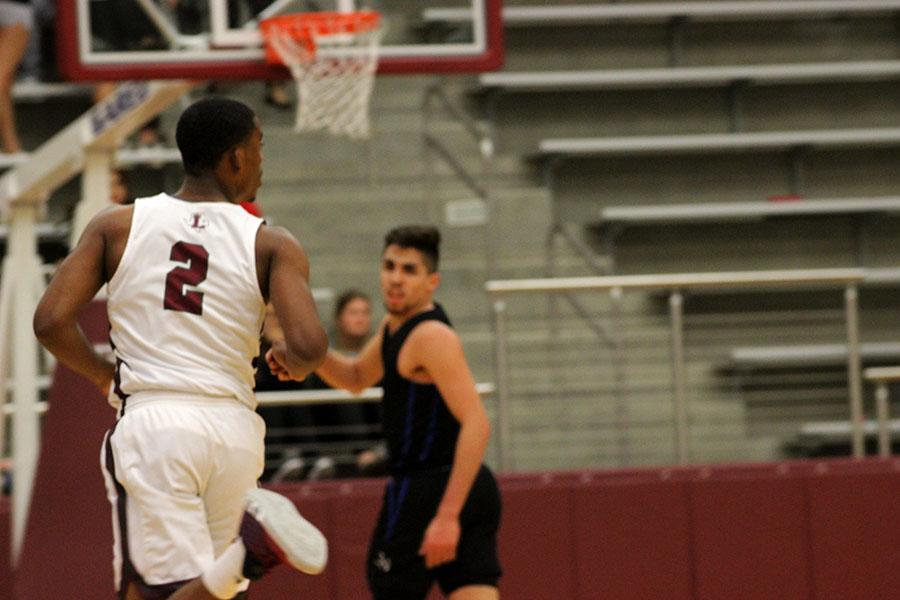 Junior+guard+Kj+Pruitt+%282%29+guards+the+hoop.