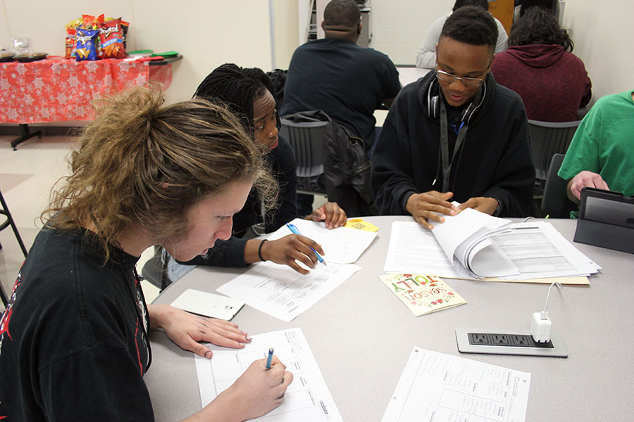 Senior Nala Hemingway and juniors Isaiah Williams and Mica Adams evaluate the research they've done for their project during class on Wednesday, Dec. 19.