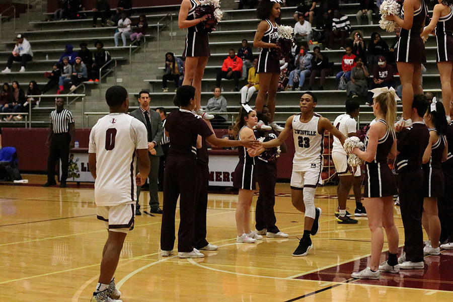 Sophomore guard Kylin Green (23) is welcomed by the cheer squad and fellow teammate senior guard Braon Williams (0).