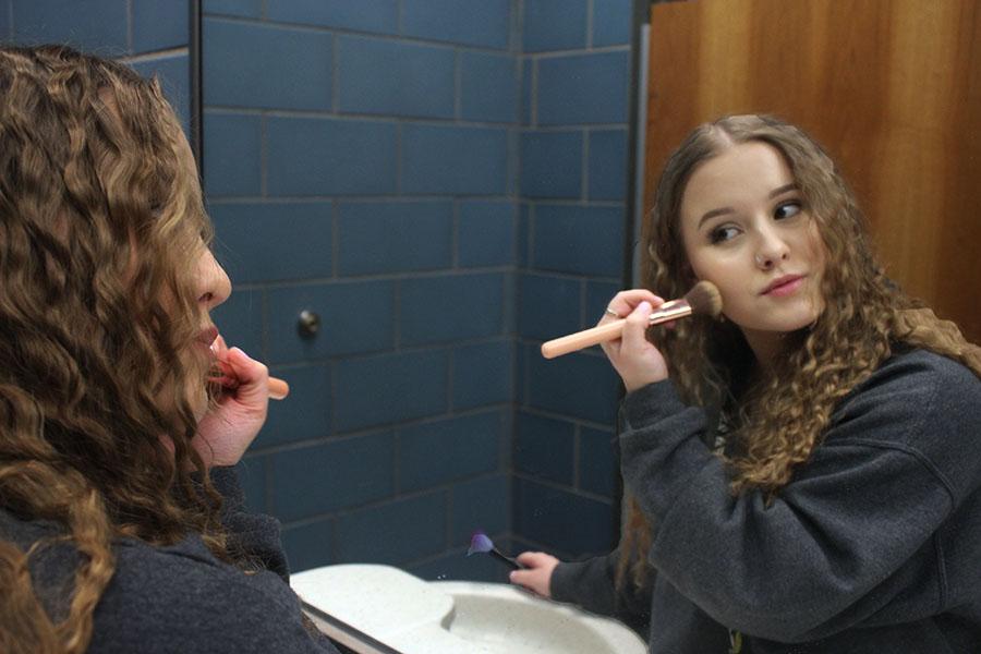 Senior Madyson Fletcher applies her highlighter with a makeup brush.