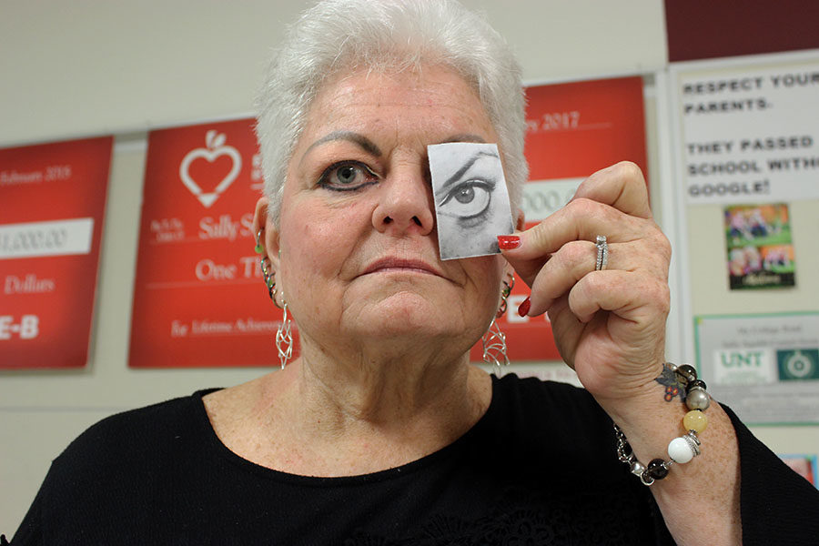 Debate+teacher+Sally+Squibb+holds+a+picture+of+her+eye+she+had+surgery+on.