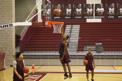 Senior Jason Lilly (24) hangs from the rim while dunking a ball during fourth period basketball practice on Tuesday, Jan. 29.