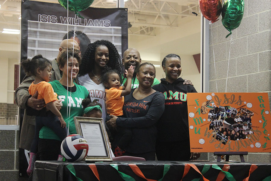 Senior Isis Williams poses for a picture with her family beside her.