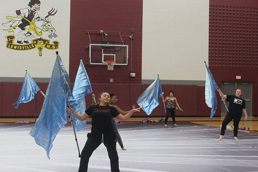 Senior Zaira Beltran rehearses the end of the performance with other winter guard members on Wednesday, Feb. 27.