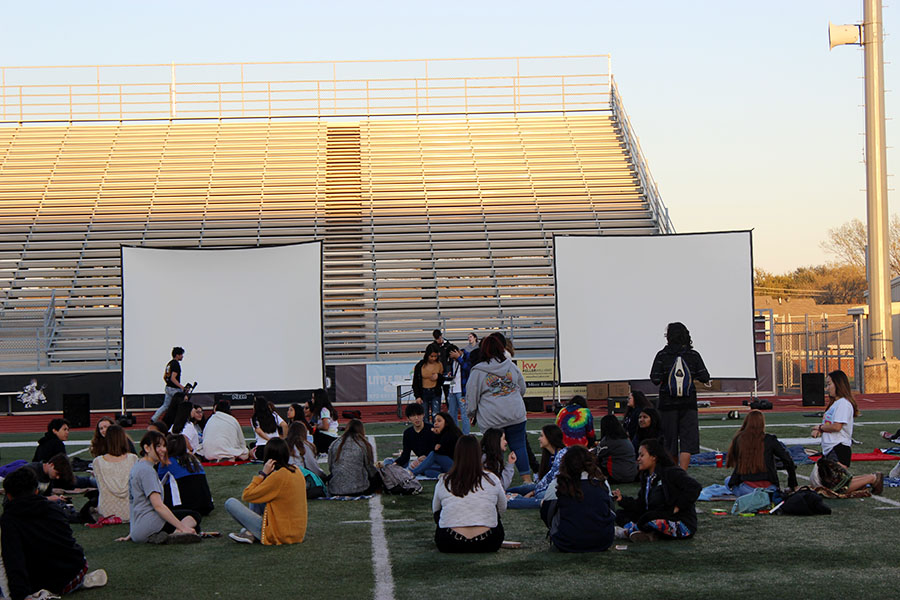 Students from all five high schools try to find open spots to sit before the movie starts on Wednesday, March 20.