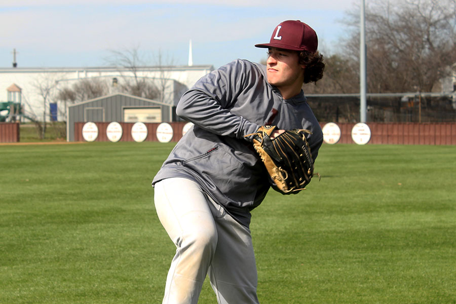Senior captain Caleb Vuono (9) practices pitching on Wednesday, March 6 during fourth period.
