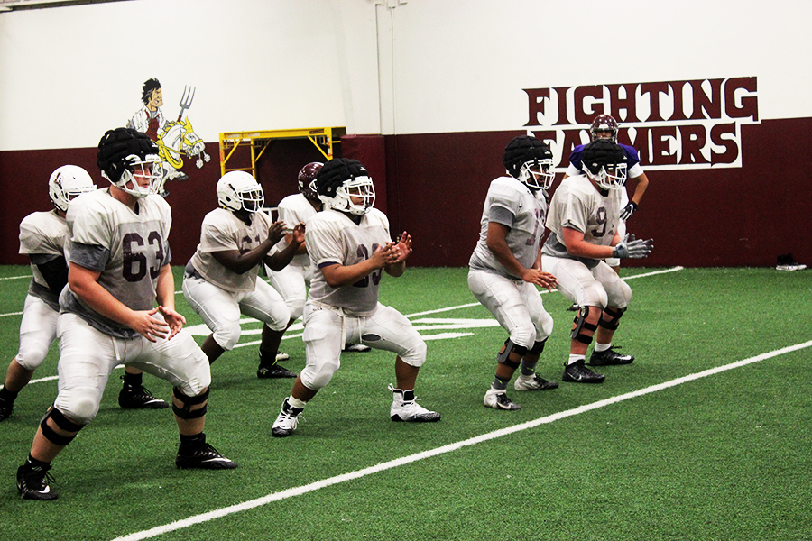 The defensive linemen practice to spring into position after the ball is spiked after school on Wednesday, April 24.