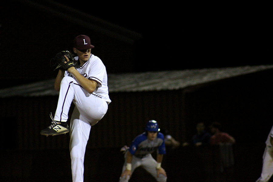 Senior Tony Rochette (7) winds up to pitch the ball at a Hebron player.