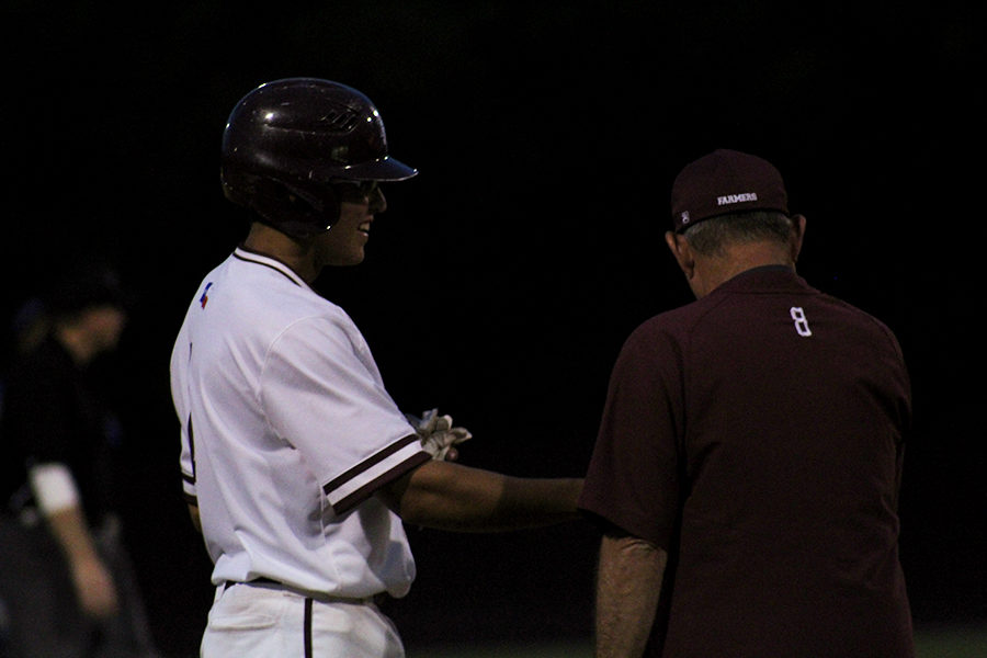 Baseball+head+coach+Mike+Campbell+discusses+game+strategy+with+junior+Kevin+Anderson+%281%29+during+the+home+game+against+Hebron+on+Tuesday%2C+April+16.