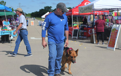 Off Leash vendor Justin Ray walks his rescue dog Joe to demonstrate positive behavior to the public at the annual Paws in the Park event on Saturday, May 4.