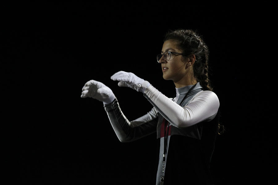Senior head drum major Sylvia Nalbandian conducts during the band's halftime performace at the away game against Flower Mound on Friday, Sept. 27.