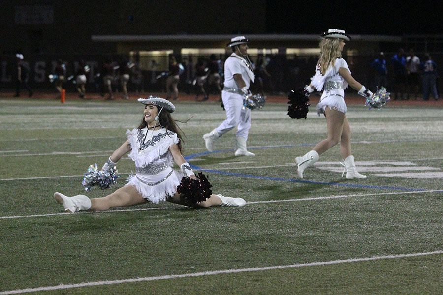Senior+Farmerette+captain+Taylor+Dill+does+a+jump+split+during+the+halftime+performance.