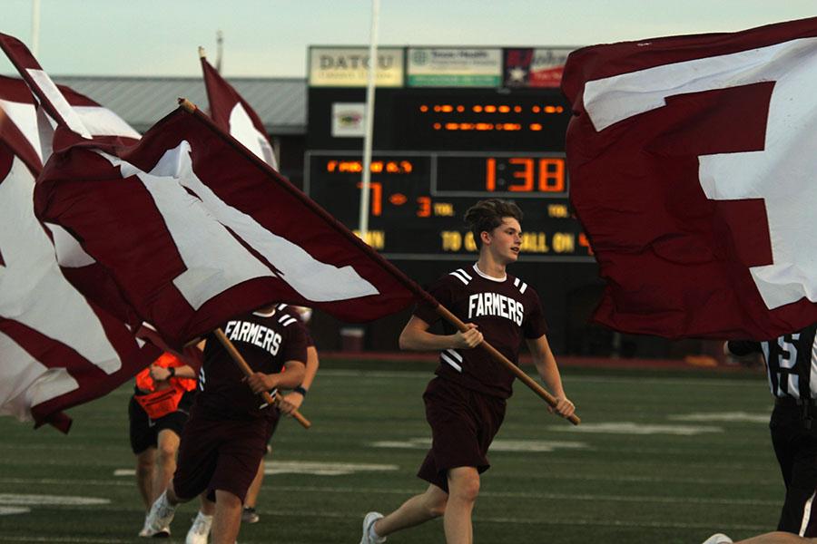 Senior+cheer+captain+Caleb+Tate+runs+and+waves+one+of+the+Farmer+flags.