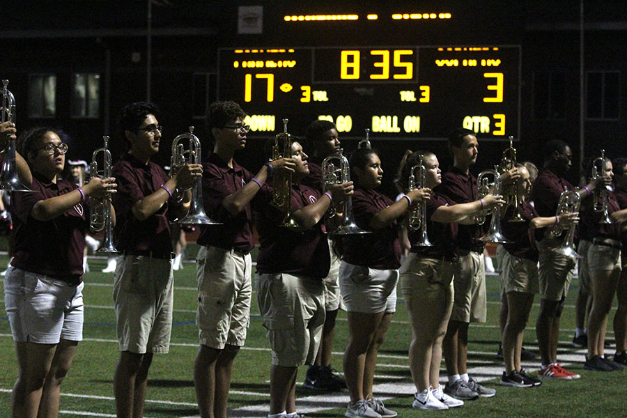 Band+members+stand+with+their+instruments+ready+to+perform+during+halftime.+