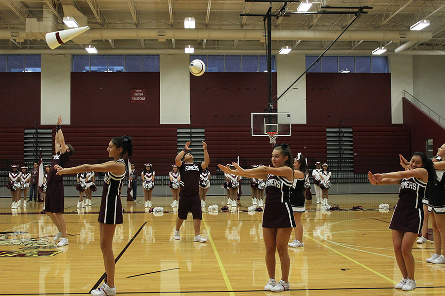 The+cheerleaders+perform+their+routine+as+they+throw+cones+in+the+air.