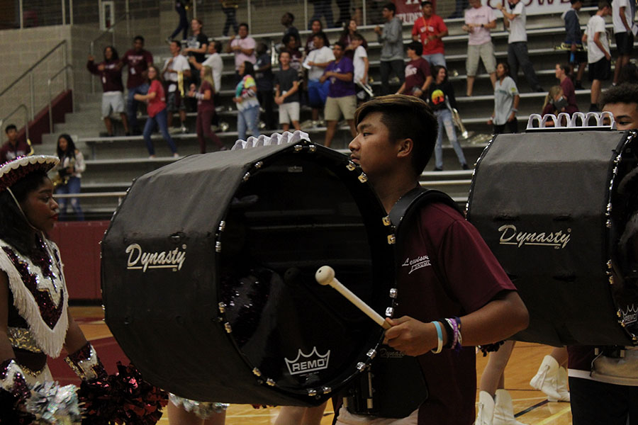 Senior+Skyler+Boonme+plays+his+bass+drum+as+he+walks+toward+the+center+of+the+arena.