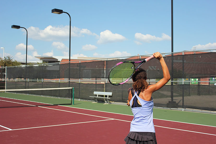 Sophomore+Amber+Rhodes+serves+a+tennis+ball+during+practice+after+school+on+Monday%2C+Sept.+17+with+the+varsity+team.